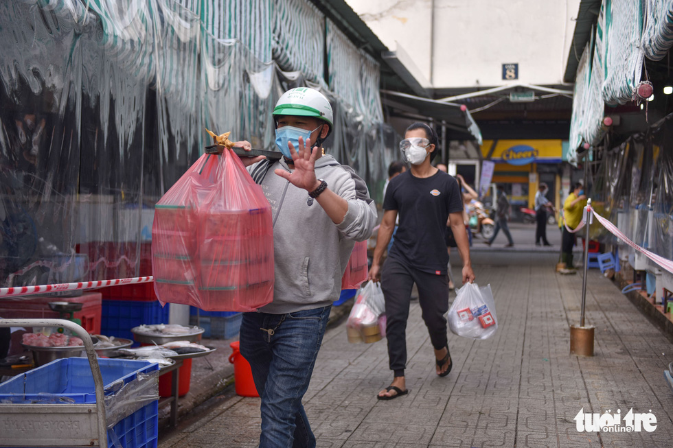 A trader is seen gesturing to express joy at the reopening of Ben Thanh Market after months of lockdown. Photo: Ngoc Phuong / Tuoi Tre