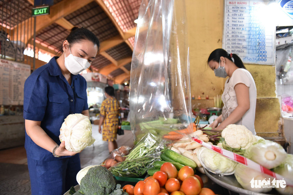 Nguyen Phuong Anh, an office employee in District 1, is seen buying vegetables at a stall in the Ben Thanh Market. Photo: Ngoc Phuong / Tuoi Tre