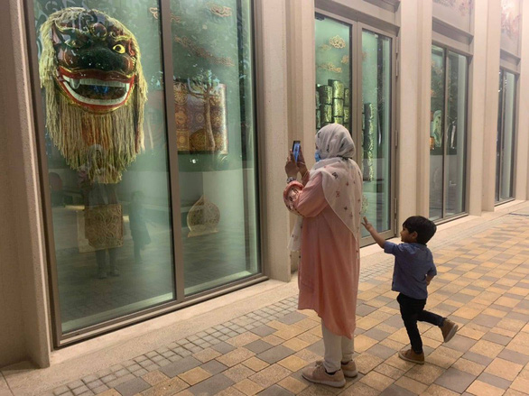 A visitor snaps some pictures of artworks at the Vietnam Pavillion in Dubai in this supplied photo.