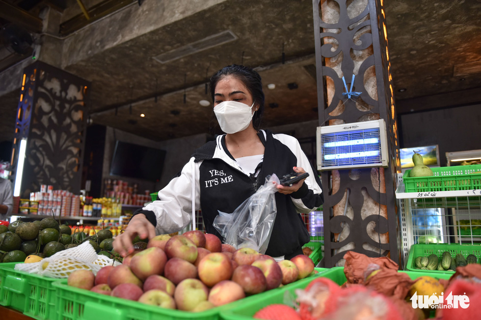A woman buys fruit from a vegetable store that was transformed from a bar on Bui Vien Street in District 1, Ho Chi Minh City. Photo: Ngoc Phuong / Tuoi Tre