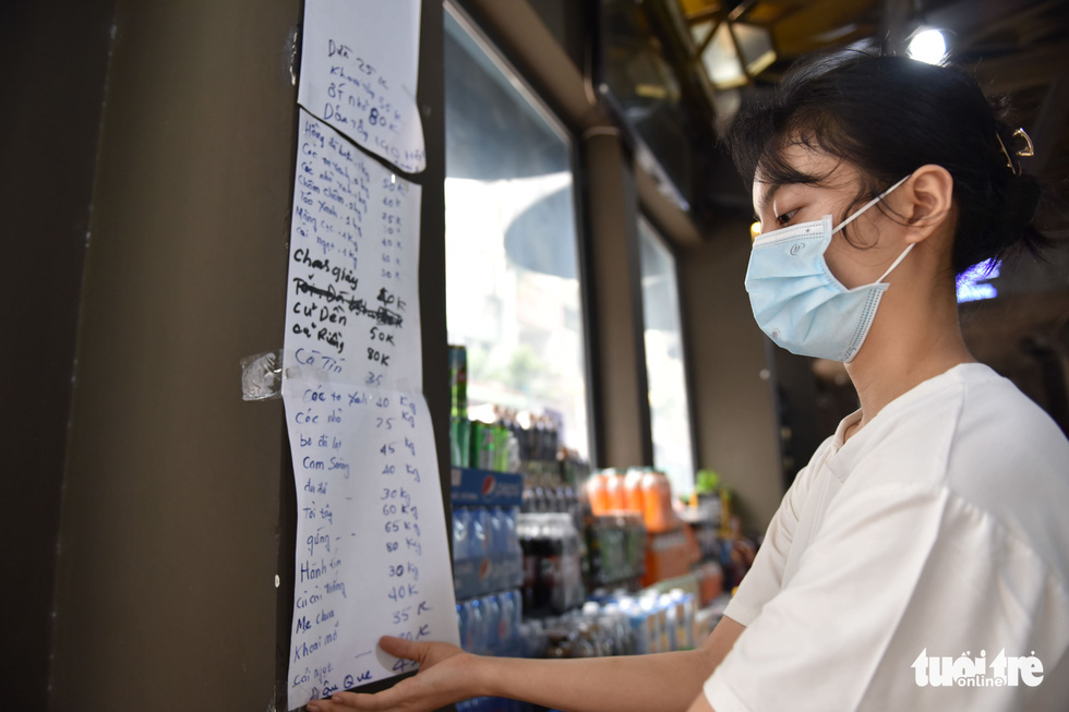 A worker creates a price list at a vegetable store that was transformed from a bar on Bui Vien Street in District 1, Ho Chi Minh City. Photo: Ngoc Phuong / Tuoi Tre