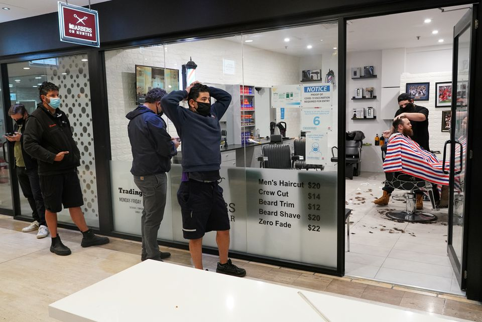 Customers wait in line at a city centre barber shop on the first day of many such businesses re-opening to vaccinated patrons, following months of lockdown orders that closed businesses to curb an outbreak of the coronavirus disease (COVID-19), in Sydney, Australia, October 11, 2021. Photo: Reuters