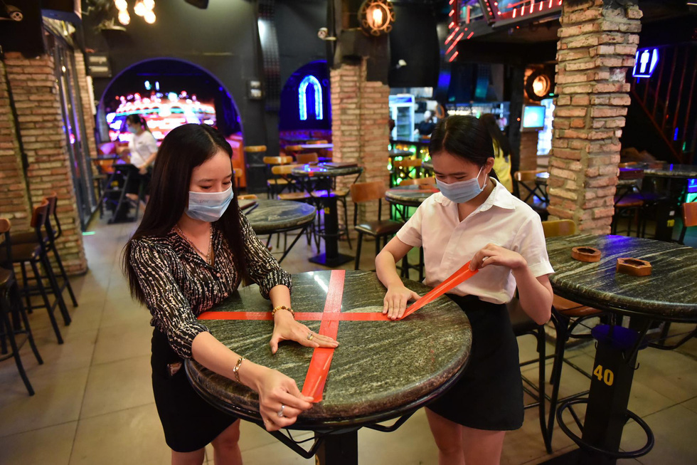 Staff mark tables to ensure distancing to prevent COVID-19 spread at Miss Saigon bar on Bui Vien Street in Ho Chi Minh City's District 1 on September 7, 2020. Photo: Ngoc Phuong / Tuoi Tre