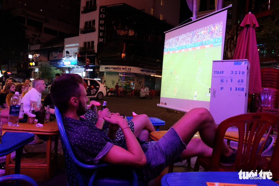 A man (foreground) sprawls in a chair while watching a 2018 FIFA World Cup game at a bar on Ho Chi Minh City's Bui Vien Street on June 29, 2018. Photo: Ngoc Dong / Tuoi Tre