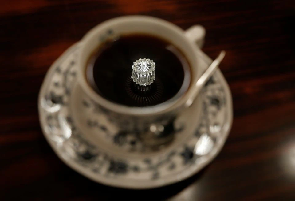 A jewelry-shaped lamp on the ceiling is reflected on a cup of coffee at Shizuo Mori's Heckeln coffee shop in Tokyo, Japan, October 8, 2021. Photo: Reuters