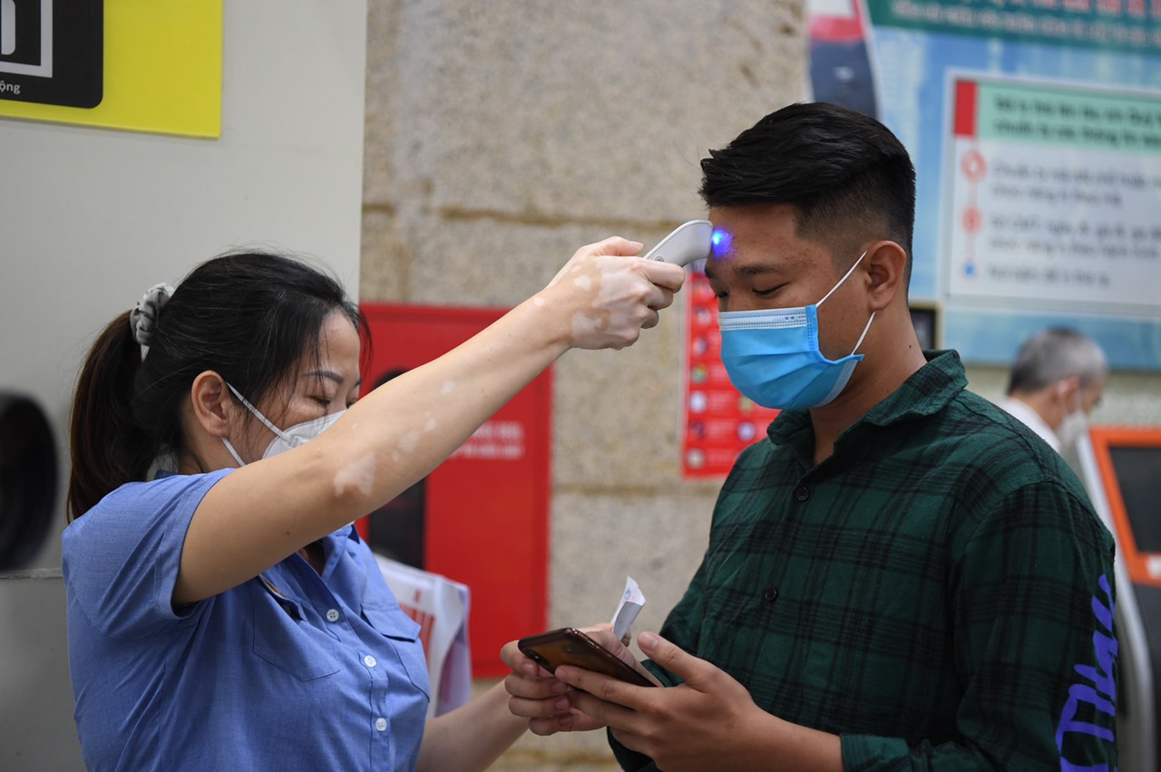 A passenger has his body temperature measured at Hanoi Railway Station, October 13, 2021. Photo: Duy Hoang / Tuoi Tre