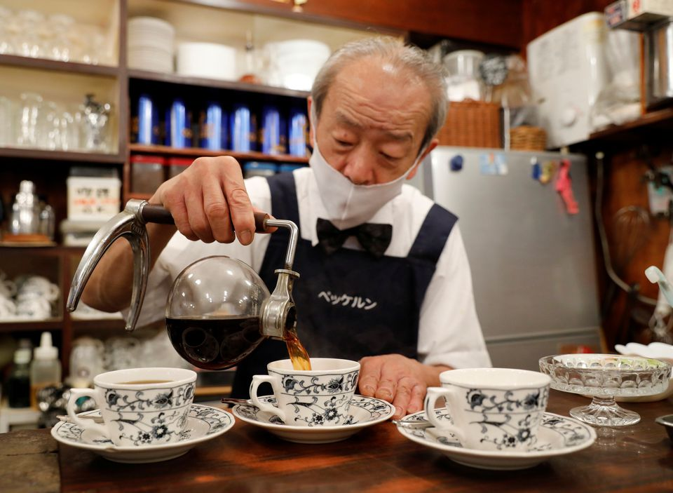 Shizuo Mori, the owner of Heckeln coffee shop pours coffee into a cup after brewing coffee with a Syphon coffee maker at his shop in Tokyo, Japan, October 8, 2021. Photo: Reuters