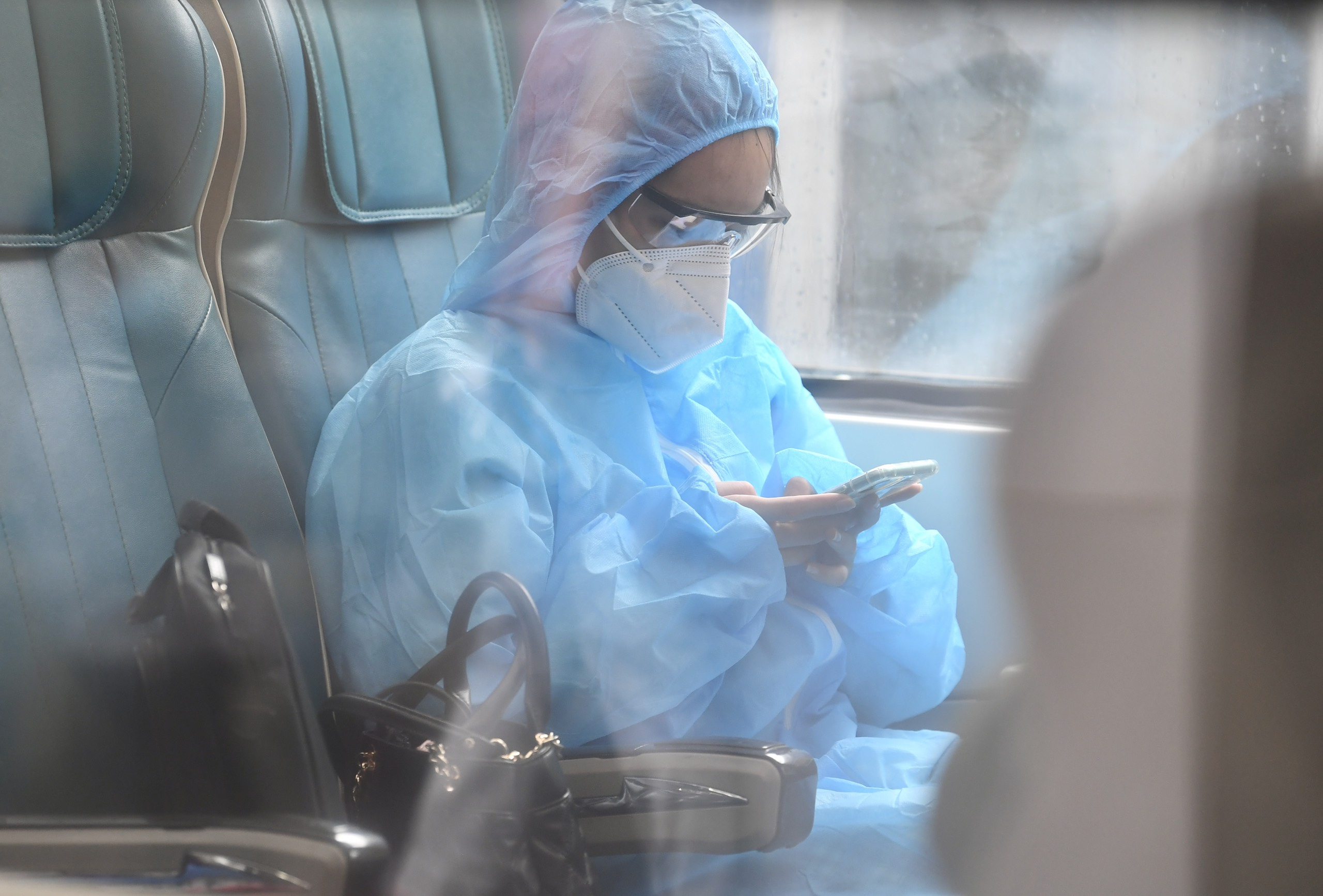 A passenger puts on face mask and protective clothing to protect herself on the SE5 train at Hanoi Railway Station, October 13, 2021. Photo: Duy Hoang / Tuoi Tre